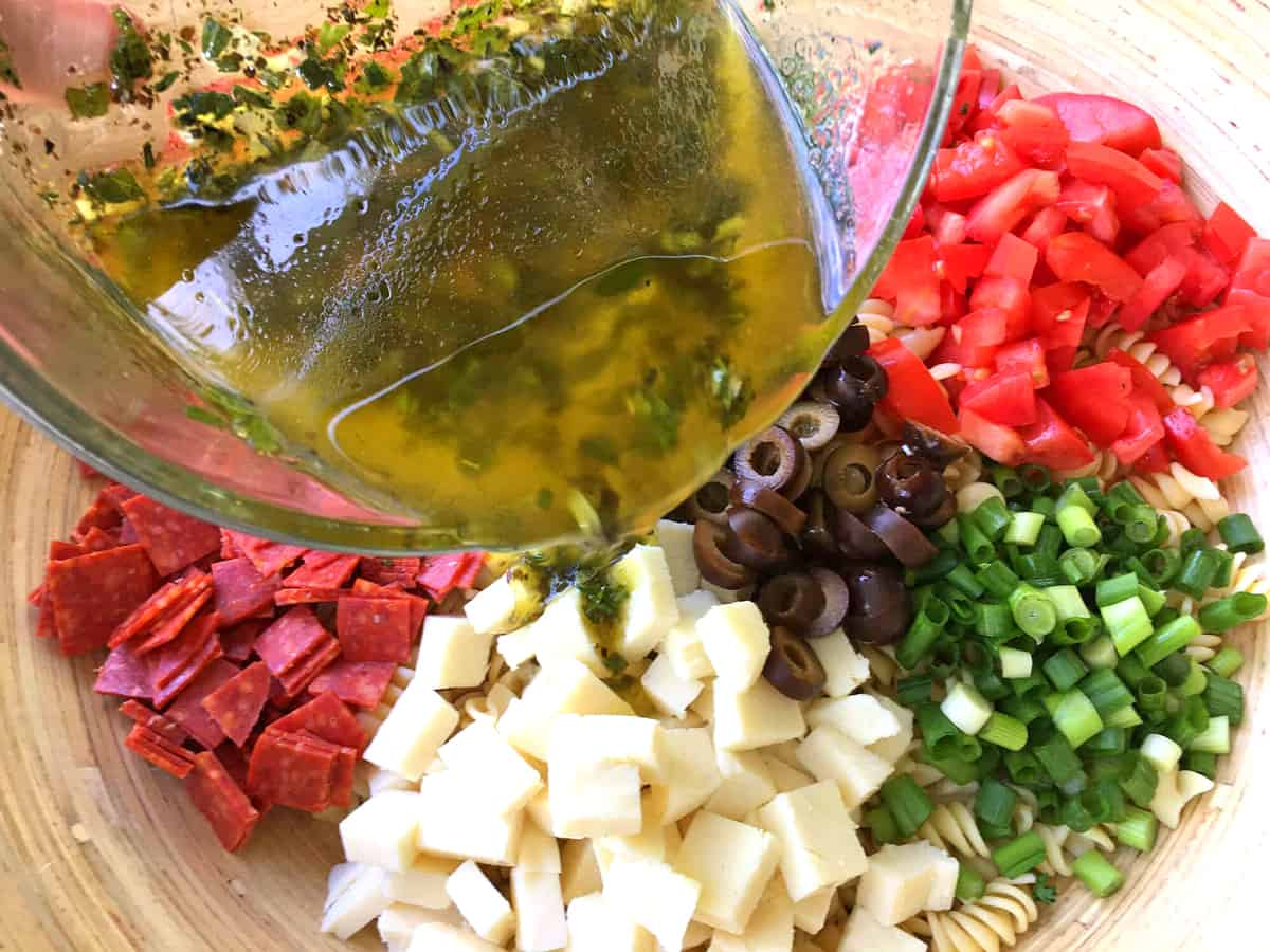 pouring vinaigrette over ingredients